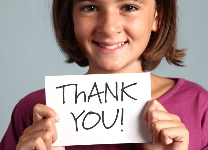 The Dreaded Mitzvah Thank You Notes girl holding a thank you card.
